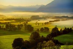 Lansdcape strabiliante di mattina di piccolo villaggio bavarese coperto in nebbia Vista scenica delle alpi bavaresi ad alba con i Fotografia Stock