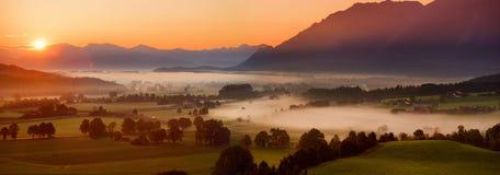 Lansdcape strabiliante di mattina di piccolo villaggio bavarese coperto in nebbia Vista scenica delle alpi bavaresi ad alba con i Fotografia Stock Libera da Diritti