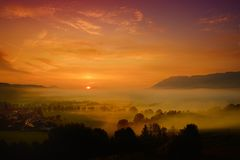 Lansdcape strabiliante di mattina di piccolo villaggio bavarese coperto in nebbia Vista scenica delle alpi bavaresi ad alba con i Fotografie Stock Libere da Diritti