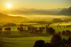 Lansdcape strabiliante di mattina di piccolo villaggio bavarese coperto in nebbia Vista scenica delle alpi bavaresi ad alba con i Immagini Stock