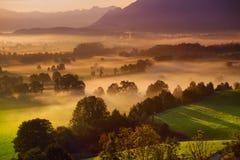 Lansdcape strabiliante di mattina di piccolo villaggio bavarese coperto in nebbia Vista scenica delle alpi bavaresi ad alba con i Immagine Stock