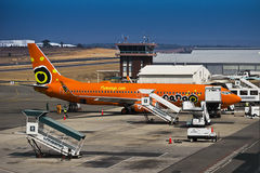 Lanseria Airport - SAA - Mango - Boeing 737-8BG. Mango (South African Airways) Boeing 737 - ZS-SJO, with the ground crew and baggage handlers in action on the Stock Photo
