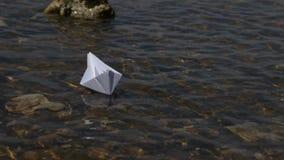 Lansering av ett pappers- fartyg på en solig dag Genomskinligt vatten som är aktuellt, bana bland hinder lager videofilmer
