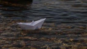 Lansering av ett pappers- fartyg p? en solig dag Genomskinligt vatten som ?r aktuellt, bana bland hinder arkivfilmer