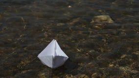 Lansering av ett pappers- fartyg p? en solig dag Genomskinligt vatten som ?r aktuellt, bana bland hinder lager videofilmer