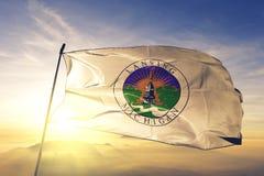 Lansing-Stadthauptstadt von Michigan des Flaggentextilstoffgewebes Vereinigter Staaten, das auf den Spitzensonnenaufgangnebelnebe lizenzfreies stockbild