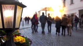 Lantaarn en bloembed tegen lopende mensen stock videobeelden