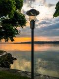 Lantaarn op de kust van het meer bij zonsondergang stock foto