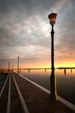Lantaarnpaal door water bij zonsondergang Royalty-vrije Stock Afbeelding