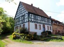 Lantbrukarhem i en liten by i Tyskland med en gå bana som leder in i skogen arkivfoton