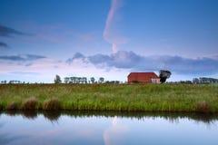 Lantbrukarhem vid kanalen i holländsk jordbruksmark Arkivfoton