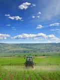 Lantbruktraktor som plogar och besprutar på fält royaltyfria bilder
