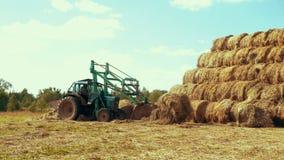 Lantbruktraktoren som transporterar sugrör, rullar på lantligt fält jordbruks- industri lager videofilmer