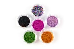Lantejoulas para pregos de cores diferentes em uma variedade em umas caixas em um fundo branco imagem de stock royalty free