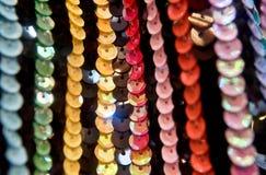 Lantejoulas redondas coloridas na tela de confecção de malhas para fundos do feriado imagem de stock