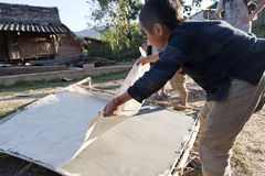 Lanten Hill Tribe Boy making Paper. A young Lanten hill tribe boy peels dried bamboo paper off the handmade paper making rack Royalty Free Stock Images