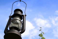 Lantern. An old oil lantern hanging on the blue sky stock photography