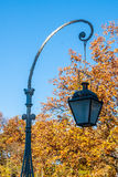 Lantern in autumn park. Street lamp against the sky and autumn trees Royalty Free Stock Images