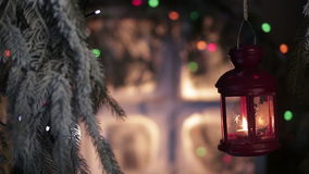 Lantern on a background of snow-covered window with Christmas lights. Winter exterior of a country house with Christmas decorations. HD stock video footage