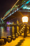 The lantern on the bank of Moskva river. The bright lantern illuminates the bank of Moskva river with Bohdan Khmelnytsky bridge on background, Moscow, Russia Royalty Free Stock Image