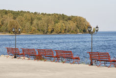 Lantern and benches on the lakeside promenade. Lantern and red bench on the autumn lakeside promenade stock photography
