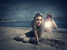 Lantern. A blonde girl sits at the beach holding a lantern in her hand Royalty Free Stock Photos