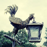 Lantern bronze cock statue in the park. Royalty Free Stock Photography