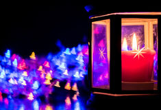 Lantern with burning candle on the background of bokeh in the form of Christmas trees Stock Images