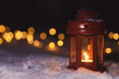 Lantern with burning candle and Christmas lights on snow outdoors. Space for text. Lantern with burning candle and Christmas lights on white snow outdoors. Space stock photography