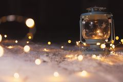 Lantern with burning candle and Christmas lights on snow outdoors. Space for text. Lantern with burning candle and Christmas lights on white snow outdoors. Space stock image