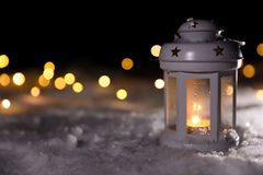 Lantern with burning candle and Christmas lights on snow outdoors. Space for text. Lantern with burning candle and Christmas lights on white snow outdoors. Space stock photo