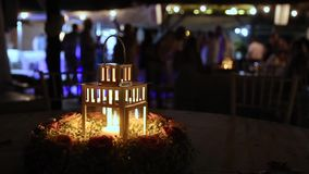 Lantern with burning candle at night. Lantern with burning candle inside on table outside at night. People dancing and having fun behind stock video