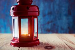Lantern with a burning candle inside on a wooden table on a dark. Blue background. Composition with copy space Stock Photography