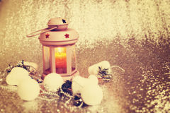 Lantern with burning candle surrounded by Christmas-tree decorat Stock Image