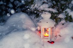 Lantern with a burning candle under a snow-covered Christmas tree in the courtyard of the house in the snowdrifts royalty free stock photo