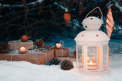 Lantern with a burning candle and wrapped gifts in the snow under the Christmas tree on Christmas Eve stock photography