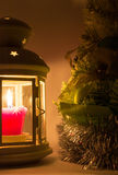Lantern with a candle burning next to the Christmas tree Royalty Free Stock Photography