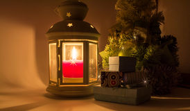 Lantern with a candle burning next to the Christmas tree Stock Photo