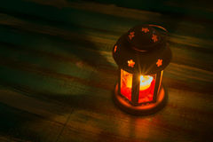 Lantern with a candle. Glare. Lantern with a candle on old wooden table. A magical evening with a wonderful light. Glare Royalty Free Stock Photo