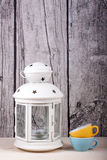 Lantern candle holder and cups vintage. On wooden royalty free stock images