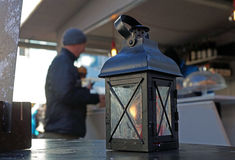 Lantern with candle and light, sundown in the mountains on the background. Royalty Free Stock Images
