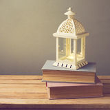 Lantern with candle and vintage books on wooden table. Christmas Celebration Royalty Free Stock Image