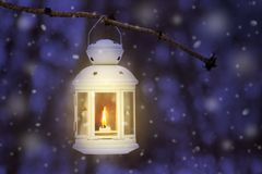 Lantern with a candle in a winter forest on a tree branch at night during snowfall_. Lantern with a candle in a winter forest on a tree branch at night during stock illustration