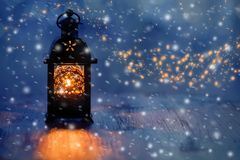 Lantern with candles on a beautiful blue background with gold dust, stars and snow. Beautiful Christmas or New Year background