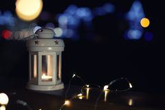 Lantern and Christmas lights on wooden railing outdoors against blurred background, space for text. Winter night stock photo