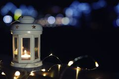 Lantern and Christmas lights on wooden railing against blurred background, space for text. Winter night. Lantern and Christmas lights on wooden railing outdoors royalty free stock photos