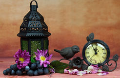 A lantern and a clock. A still life of a lantern and a clock, grapes and flowers, selective focus Stock Photo