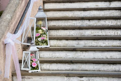 Lantern and flower wedding decorations with tulle. White and metallic lantern decorations with white and pink flowers and tulle on a stone staircase Royalty Free Stock Photos