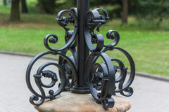 Lantern forged decorative finish. Elaborate finish the base of a streetlight Stock Images