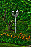 Lantern in the Gardens. A lantern found within the flowers and trees Stock Image